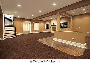 Lower level basement in earth tones and marble fireplace