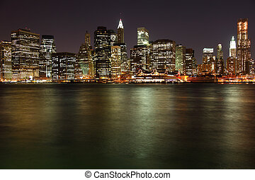 Lower Manhattan in New York City at night with reflection in...
