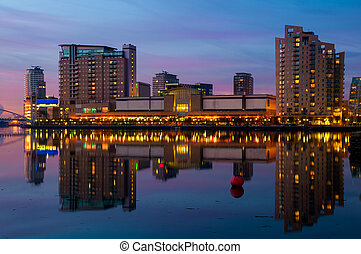 Reflection of Manchester, Salford quays skyline in water.