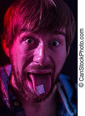LSD blotter on the tongue - Guy with LSD blotter stamp on...