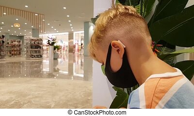 Lttle boy in a mask sits in a shopping center