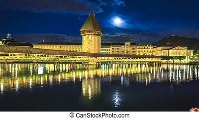 TIME-LAPSE: Kapellbrucke flowered Chapel Bridge with Water Tower reflects in Reuss river on Lake Lucerne at night. Mount Pilatus mountain overlooking Lucerne, city of Swiss bridges in Switzerland.