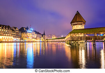 Lucerne, Switzerland, night view over the Reuss river to the wooden Chapel bridge and Water tower