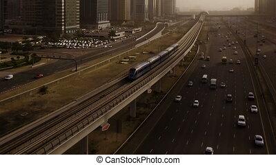 luchtmening, van, snel, treinen, blauwe , welke, reizen, door, de, viaduct, langs, de, snelweg, met, auto's, omringde, door, skyscrapers., dubai, uae
