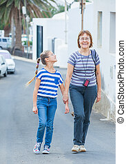 Lucky girl with her grandmother walking