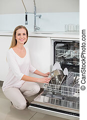 Lucky gorgeous model kneeling next to dish washer in bright...
