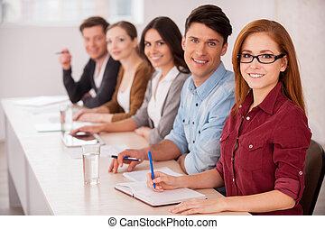 ludzie, pracujący, razem., grupa kawalerki, posiedzenie razem, na stole, i, uśmiechanie się, na aparacie fotograficzny