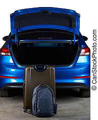 Luggage bags stand next to open car trunk