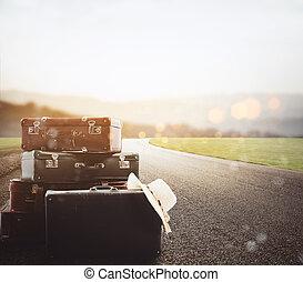 Luggage resting on asphalt