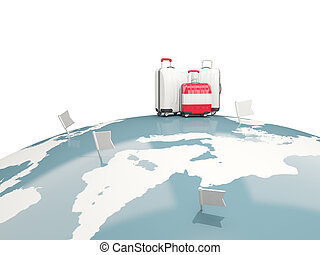 Luggage with flag of austria. Three bags on top of globe