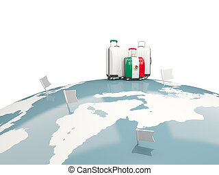 Luggage with flag of mexico. Three bags on top of globe