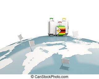 Luggage with flag of zimbabwe. Three bags on top of globe