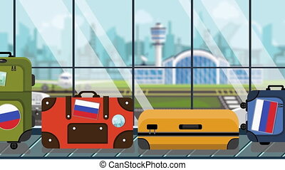 Luggage with Russian flag stickers on baggage carousel in...