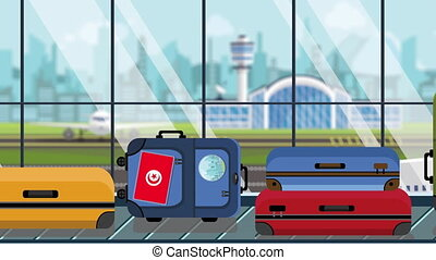 Luggage with Tunisian flag stickers on baggage carousel in...