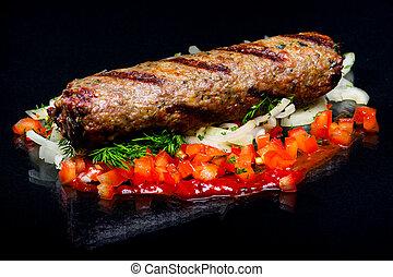 Lula kebab on a black background.