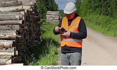 Lumberjack checking the tree bark near log of pile