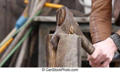 Lumberjack chopping firewood using axe, logs splitting....