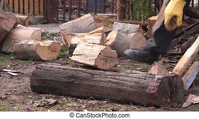Lumberjack cutting firewood logs with axe, man splitting...