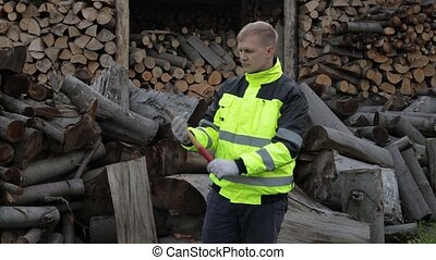 Lumberjack in reflective jacket. Man woodcutter hold small ...
