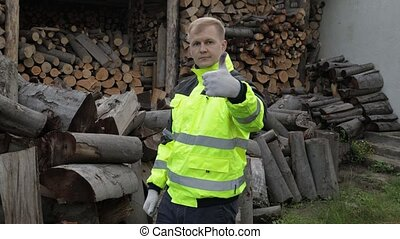 Lumberjack in reflective jacket. Man woodcutter show thumb ...