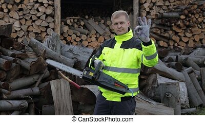Portrait of lumberjack posing in jacket with reflective stripes holds electric chainsaw. Show ok sign. Man woodcutter standing and looking at camera. Sawn logs, firewood background. Wood harvesting