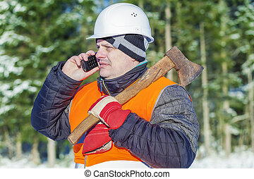 Lumberjack in the forest in winter with an ax