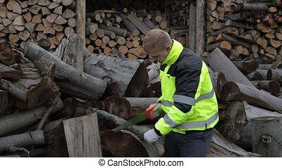 Lumberjack. Man woodcutter use small saw. Sawn logs, sawmill...