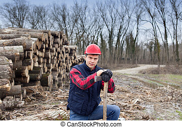Portrait of young lumberjack with ax beside cut trunks in forest