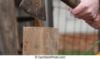 Lumberjack splitting wood and cutting firewood with old axe....