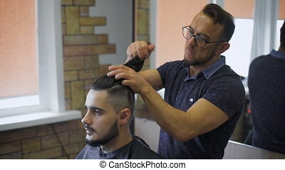 Lumberjack style. Male barber in plaid shirt combing hair of...