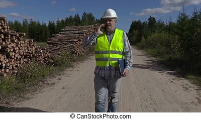 Lumberjack talking on smartphone and walking near log piles