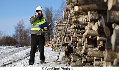 Lumberjack talking on the cell phone near at the log pile
