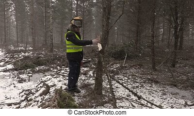 Lumberjack trying to start chainsaw in forest