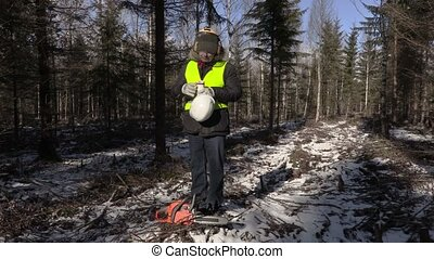 Lumberjack with chainsaw and coffee in forest in winter