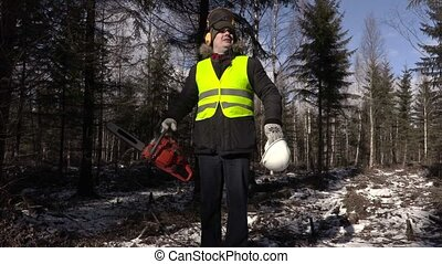 Lumberjack with chainsaw and helmet in forest with camera...