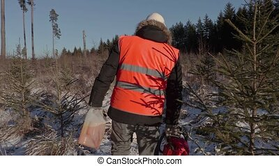 Lumberjack with chainsaw and petrol can on snow covered path