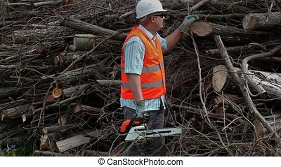 Lumberjack with chainsaw at the pile of branches