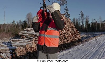 Lumberjack with chainsaw call for other workers near logs