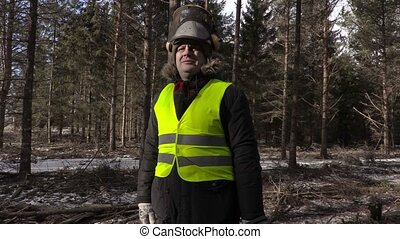 Lumberjack with chainsaw on shoulder in forest with camera...