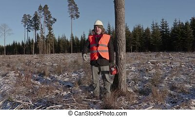 Lumberjack with chainsaw talking in forest