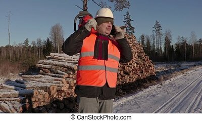 Lumberjack with chainsaw talking on phone near pile of logs in winter