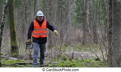 Lumberjack with chainsaw  walking in forest