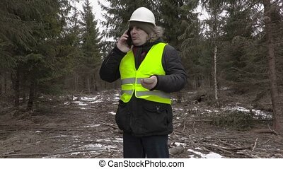Lumberjack with euro banknotes and smart phone in forest