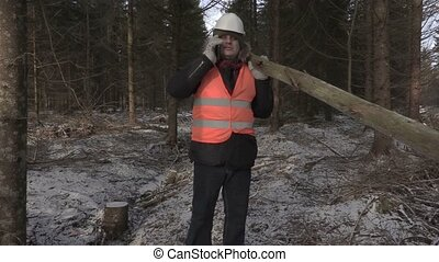 Lumberjack with log on shoulder talking on phone