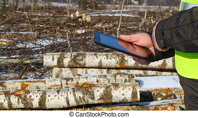 Lumberjack with tablet PC in winte