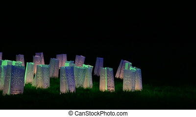 Luminaries on the grass - Paper bag candle lamps glowing in...