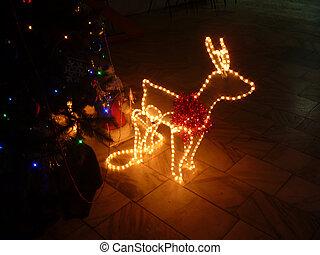 Luminous deer beside fir trees on dark background