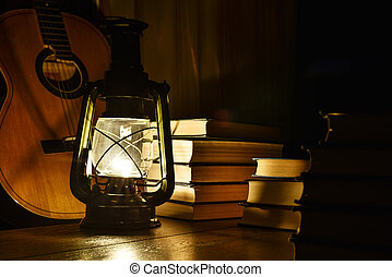 Luminous kerosene lamp, guitar and books on the table