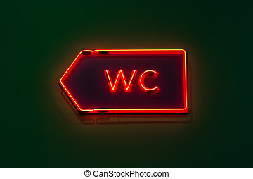 Luminous neon pointer to the WC in a public building