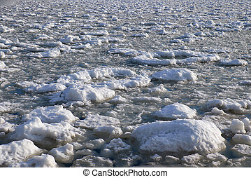 Lumps of snow and ice frazil on the surface of the freezing river water in early winter season
